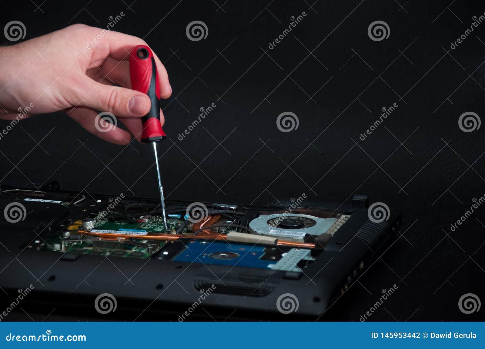 Main tenant un tournevis réparant un ordinateur portable ouvert sur le fond foncé