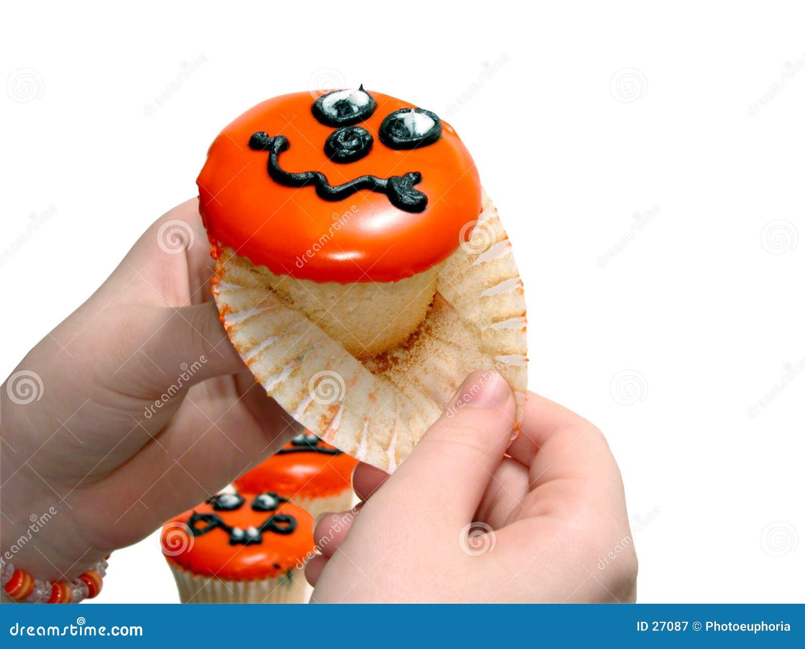 Main tirant le papier du gâteau de Veille de la toussaint
