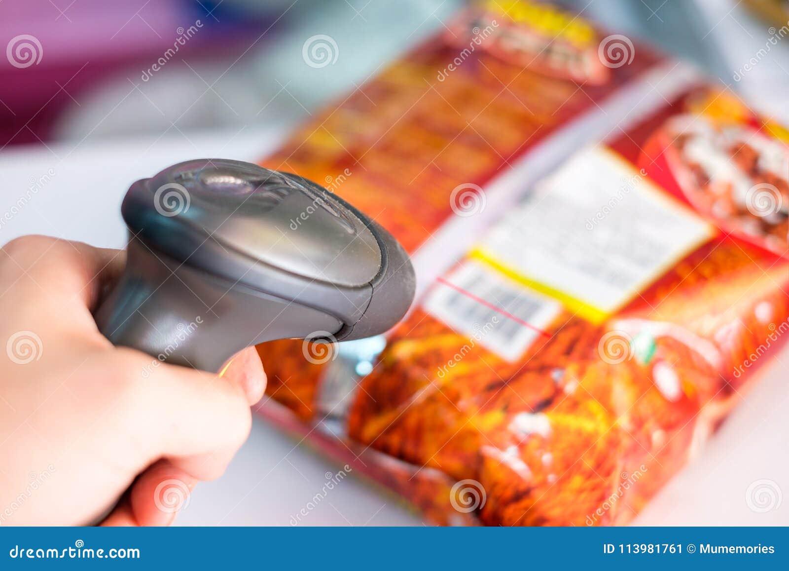 Main utilisant le code barres manuel de scanner avec l étiquette de balayage