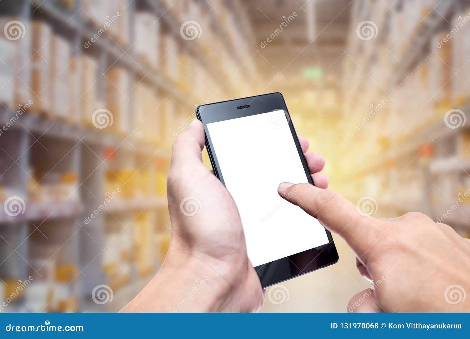 Main utilisant le smartphone avec la technologie de gestion des stocks d entrepôt