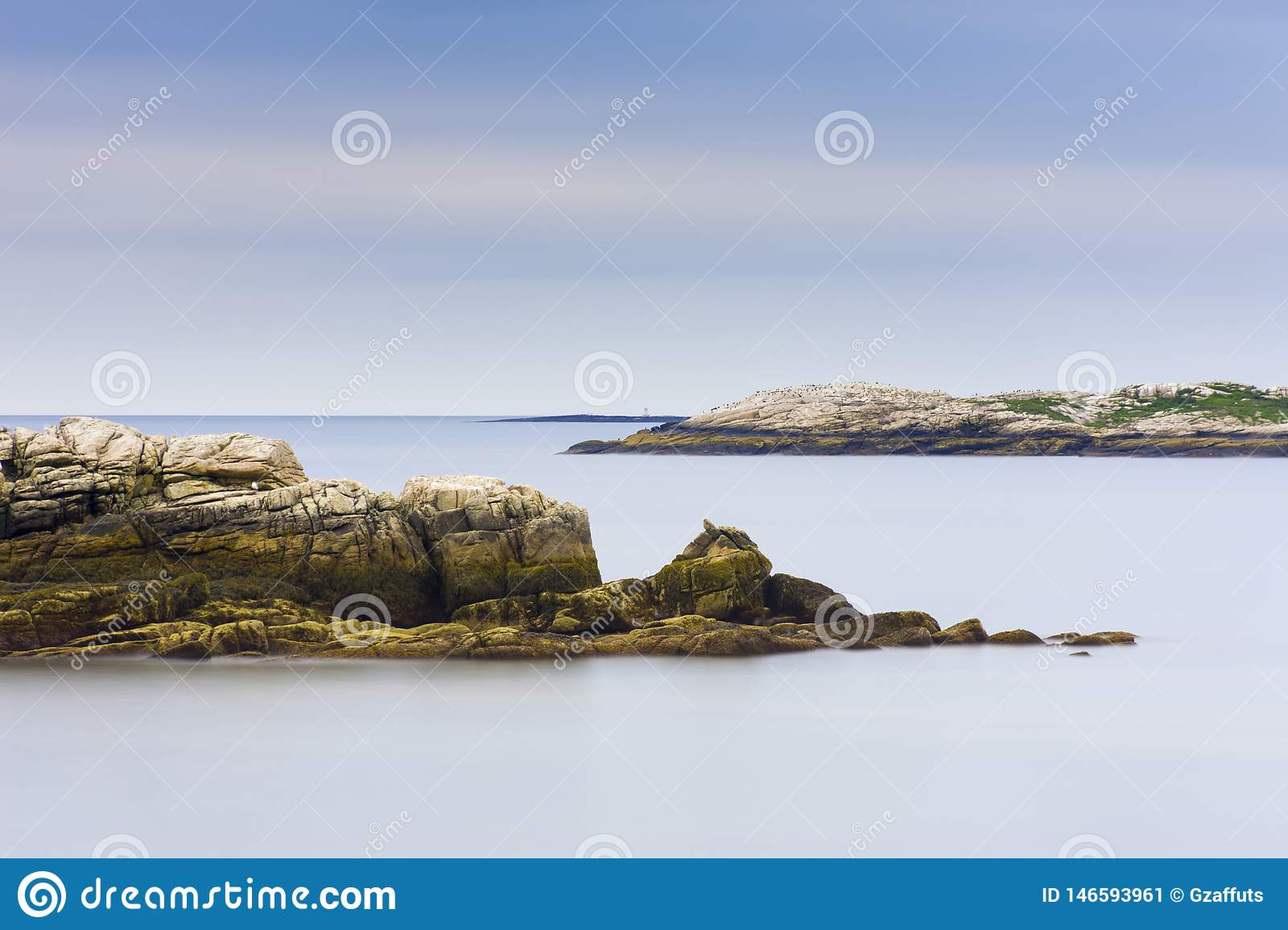 Maine rocky coast line with smooth ocean and blue sky