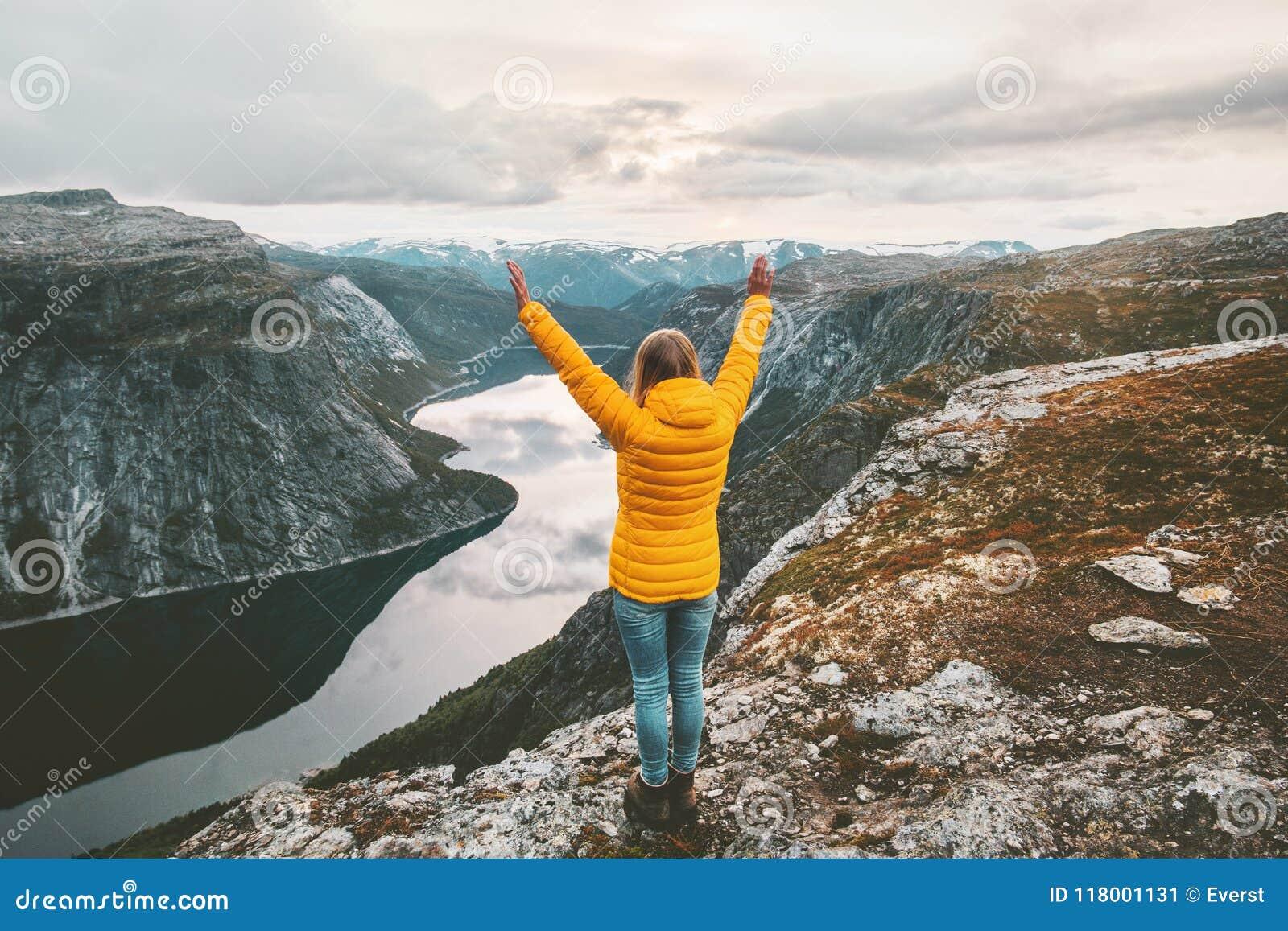 Mains augmentées par femme heureuse sur le sommet de montagne