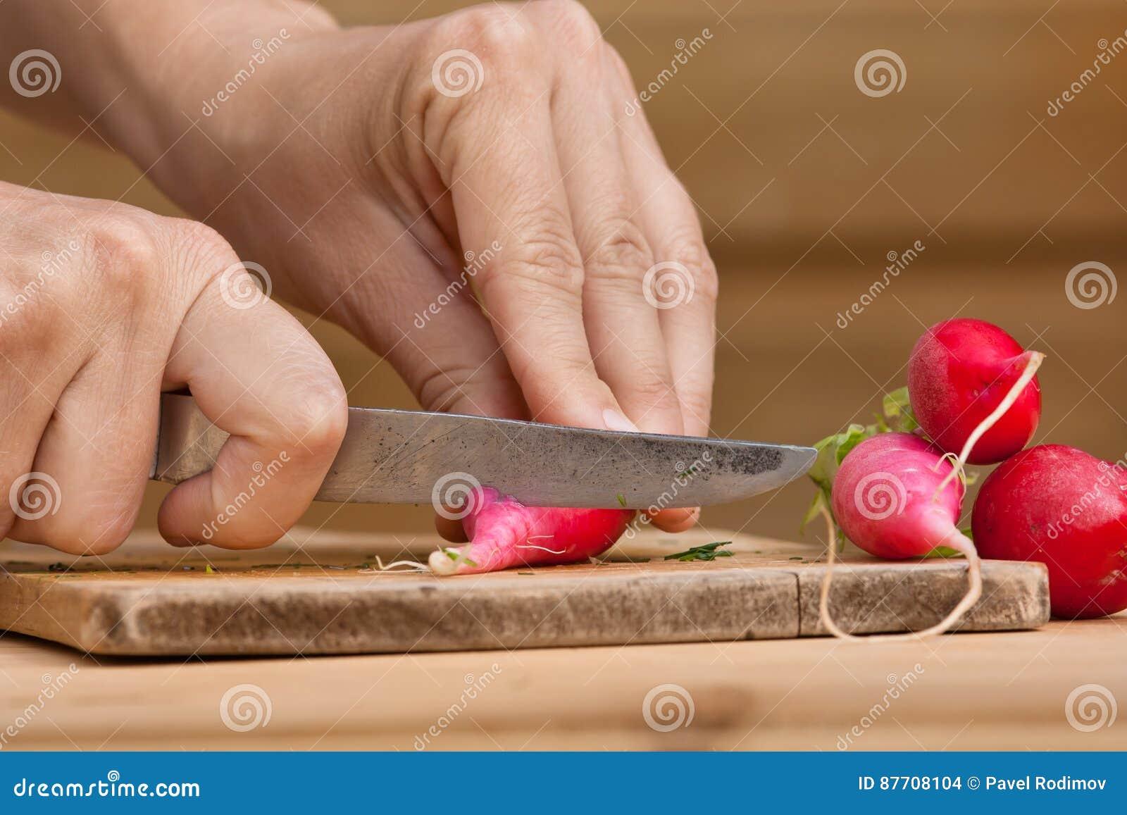Mains coupant des radis sur le hachoir