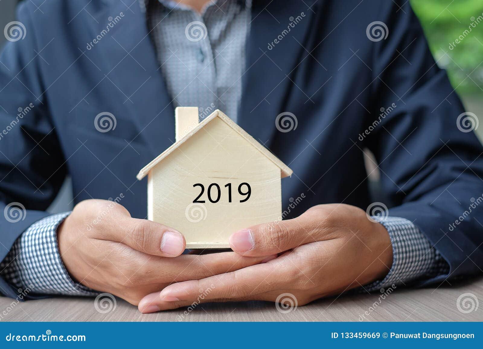 Mains d homme d affaires tenant le modèle en bois de Chambre Assurance des biens et immobiliers
