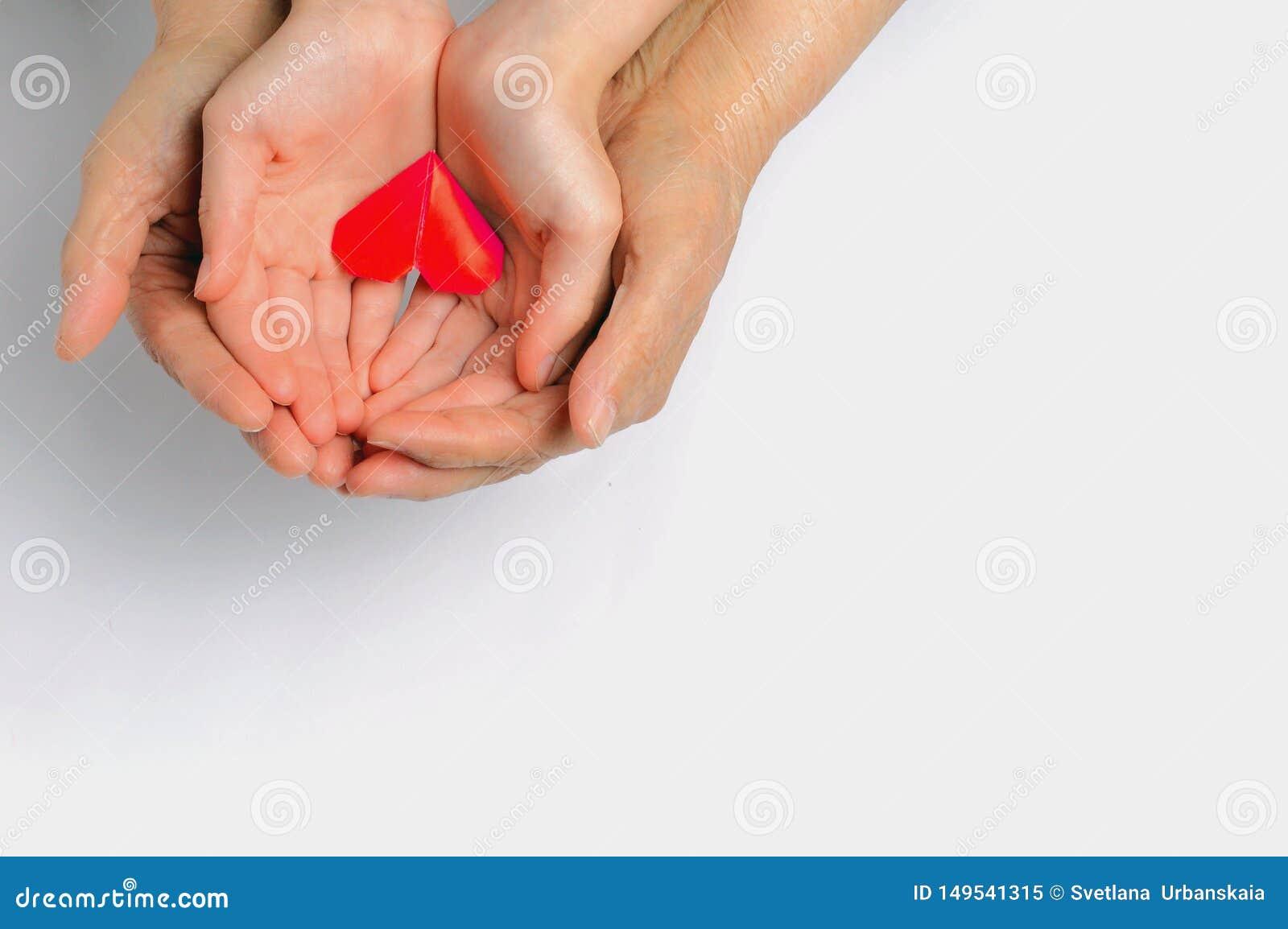 Mains d un adulte et d un enfant tenir un coeur rouge