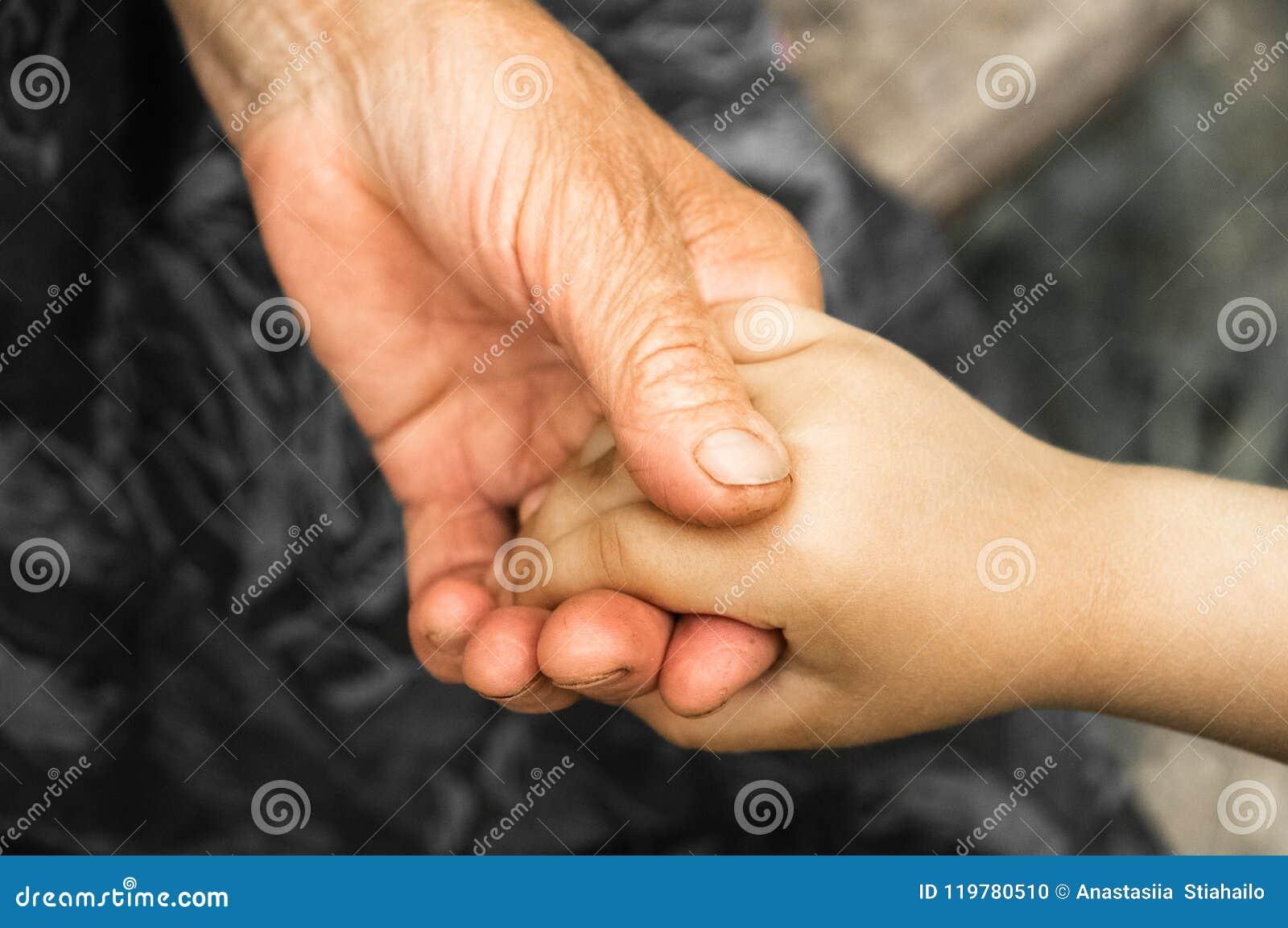 Mains d une petite fille et d une vieille grand-mère Mains de petits enfants tenant l homme plus âgé, concept de jour de gentille