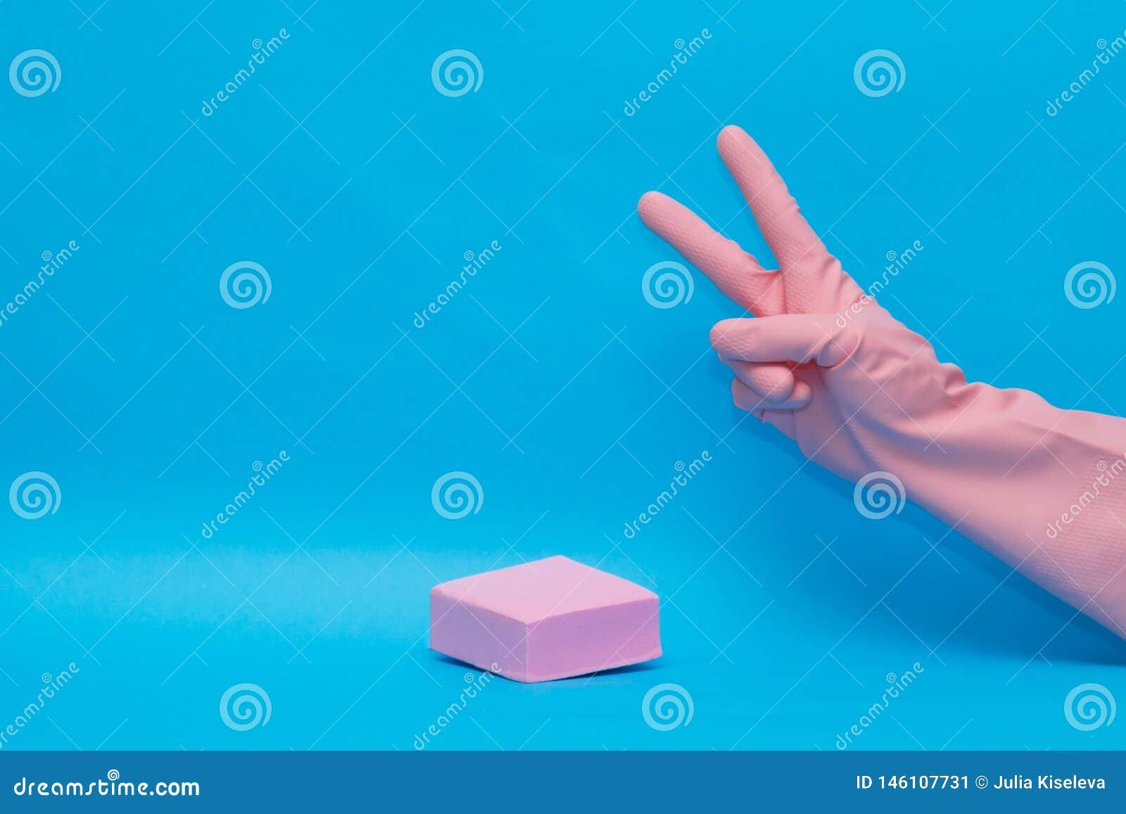 Mains dans le gant rose économique pour des produits domestiques sur le fond bleu pour la conception