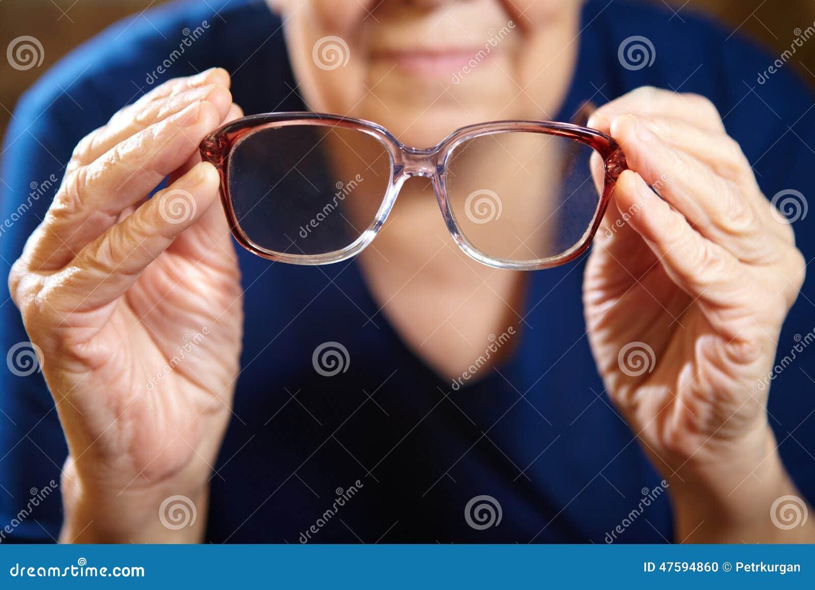 Mains de dame âgée avec des lunettes