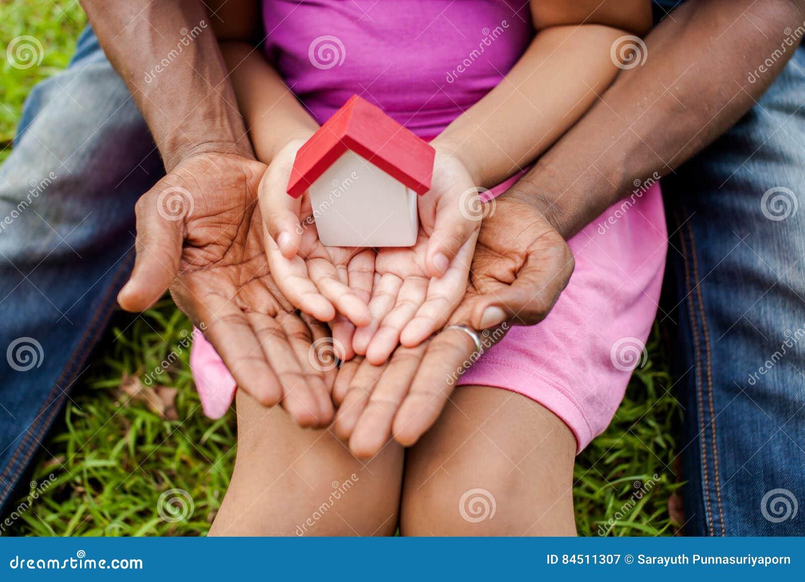 Mains de famille tenant ensemble la maison en parc vert - famille ho