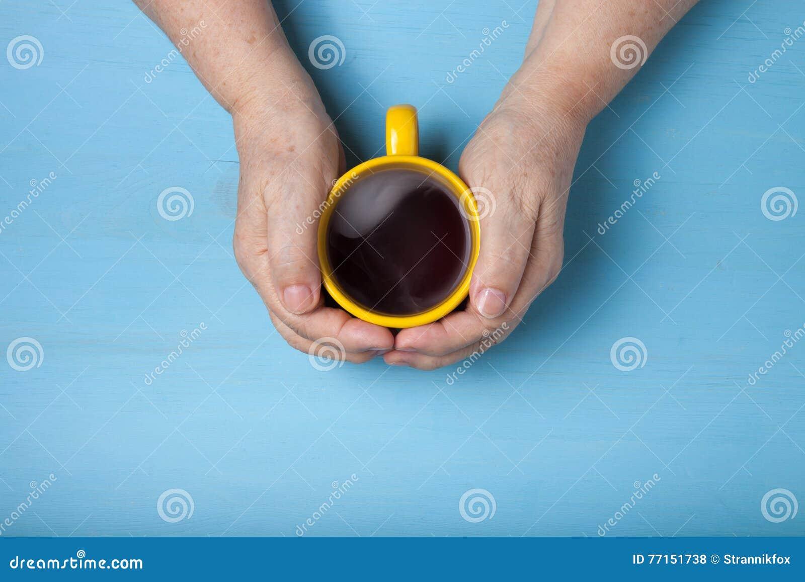 Mains de femme agée sur le fond en bois