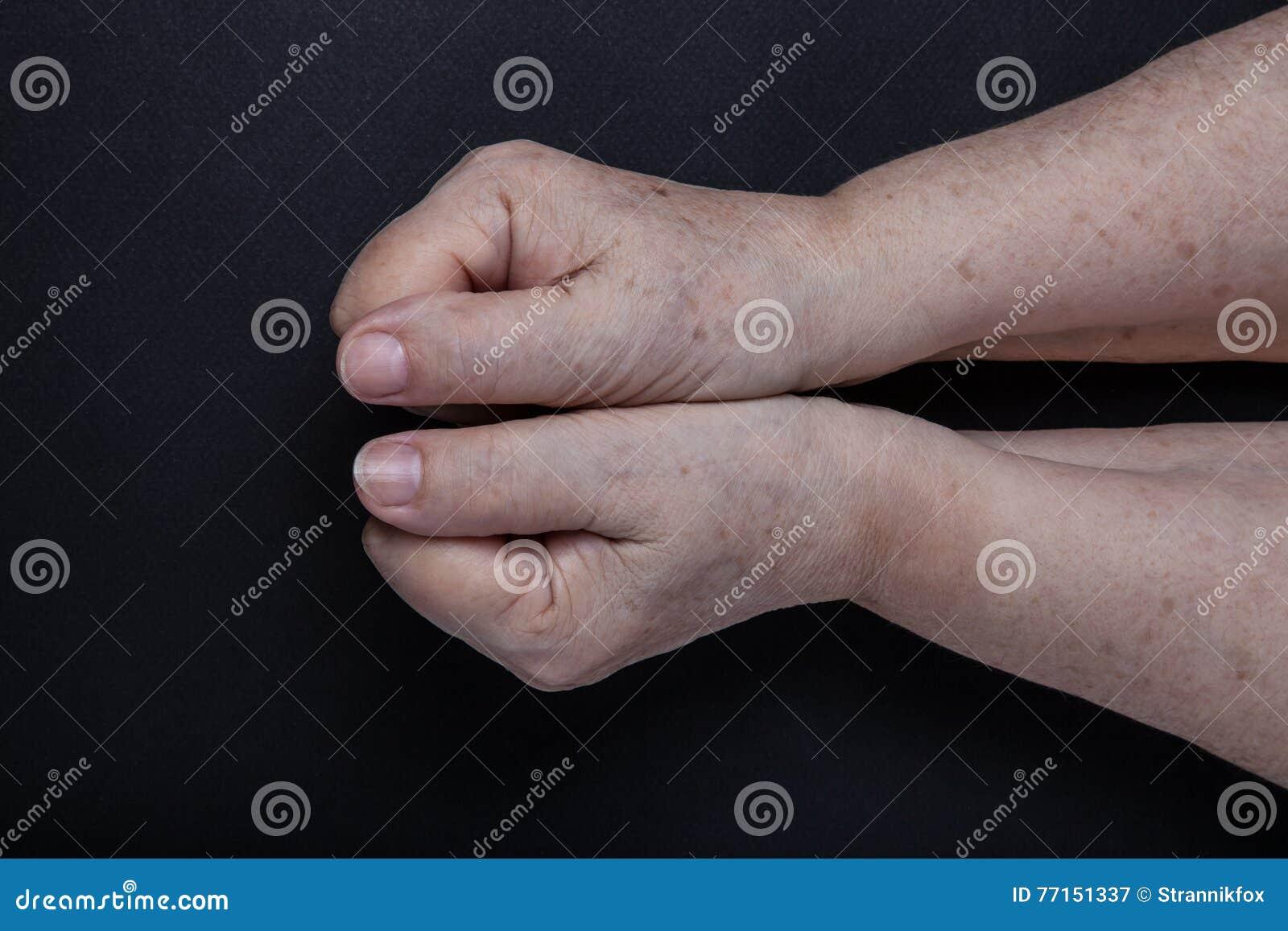 Mains de femme agée sur le fond noir