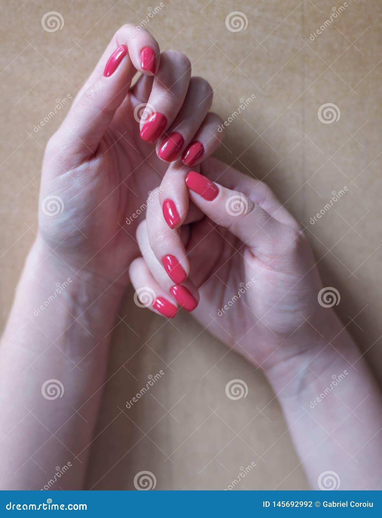 Mains de femme avec la manucure rouge