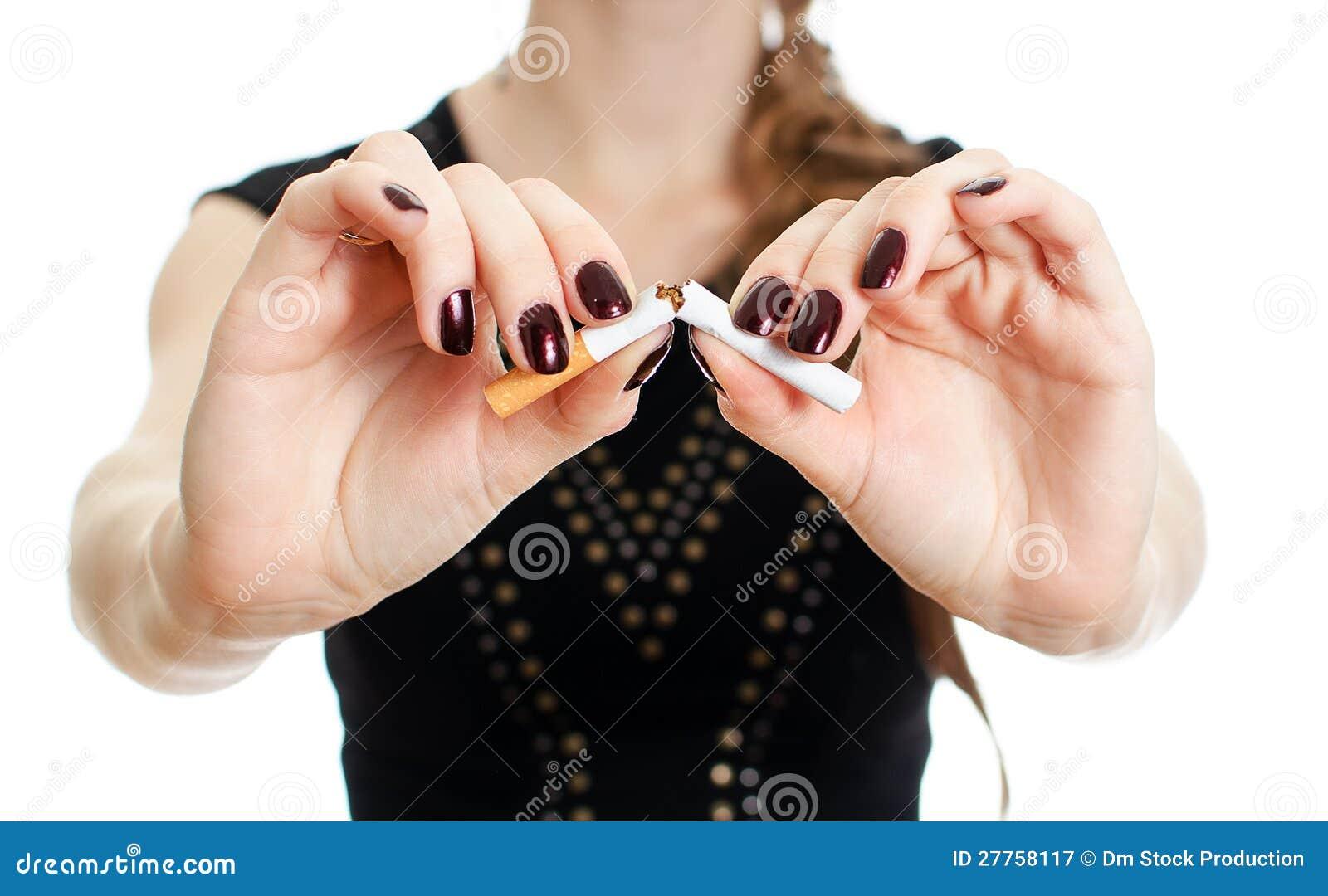 Mains de femme cassant la cigarette.