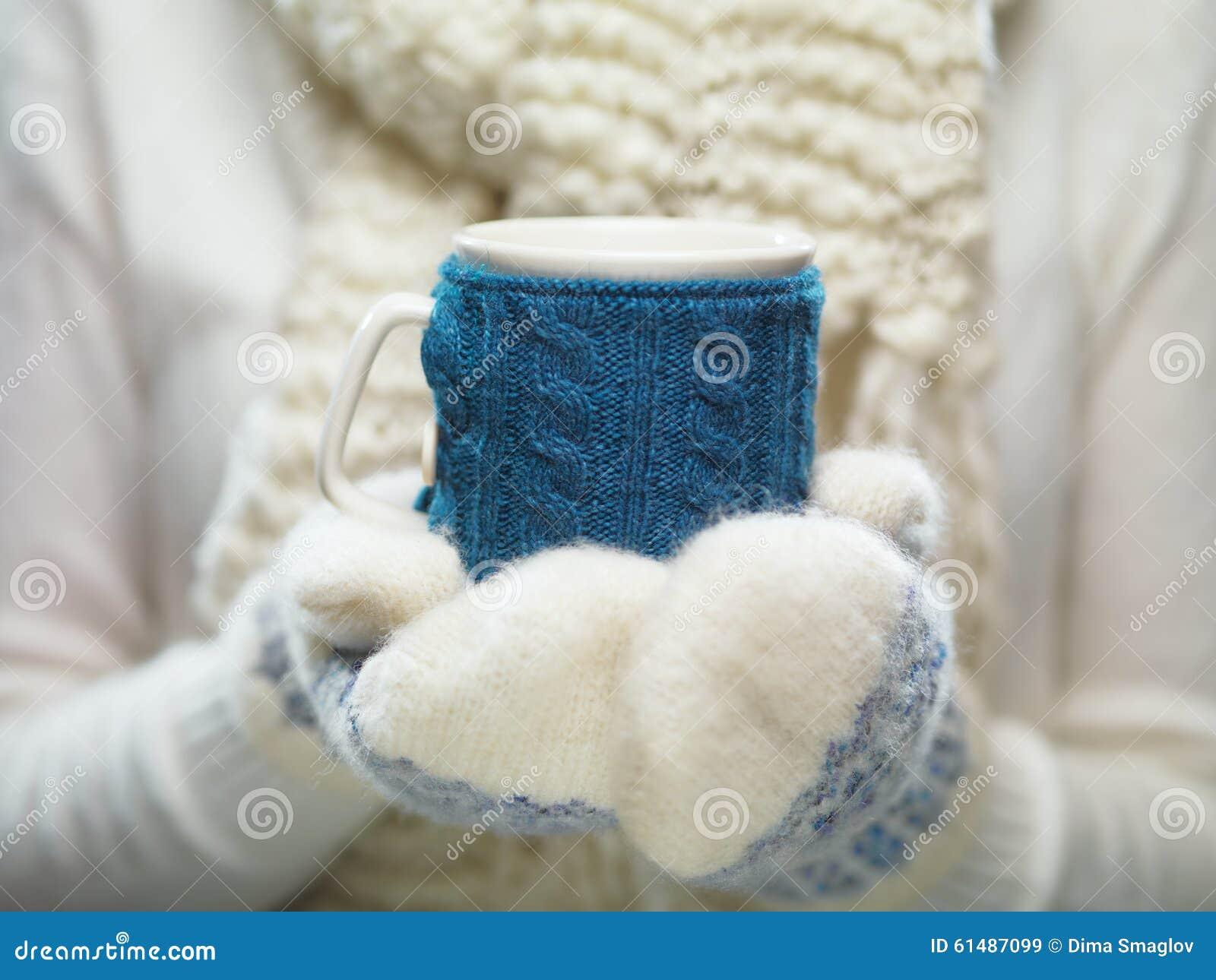Mains de femme dans des mitaines blanches et bleues tenant une tasse tricotée confortable avec du cacao, le thé ou le café chaud