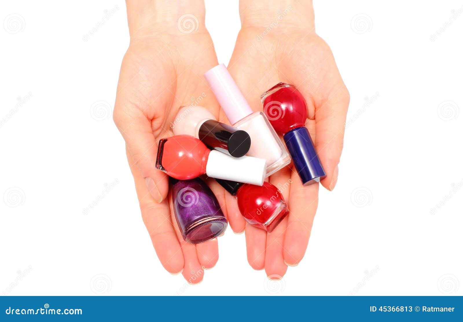 Mains de femme et de vernis à ongles sur le fond blanc