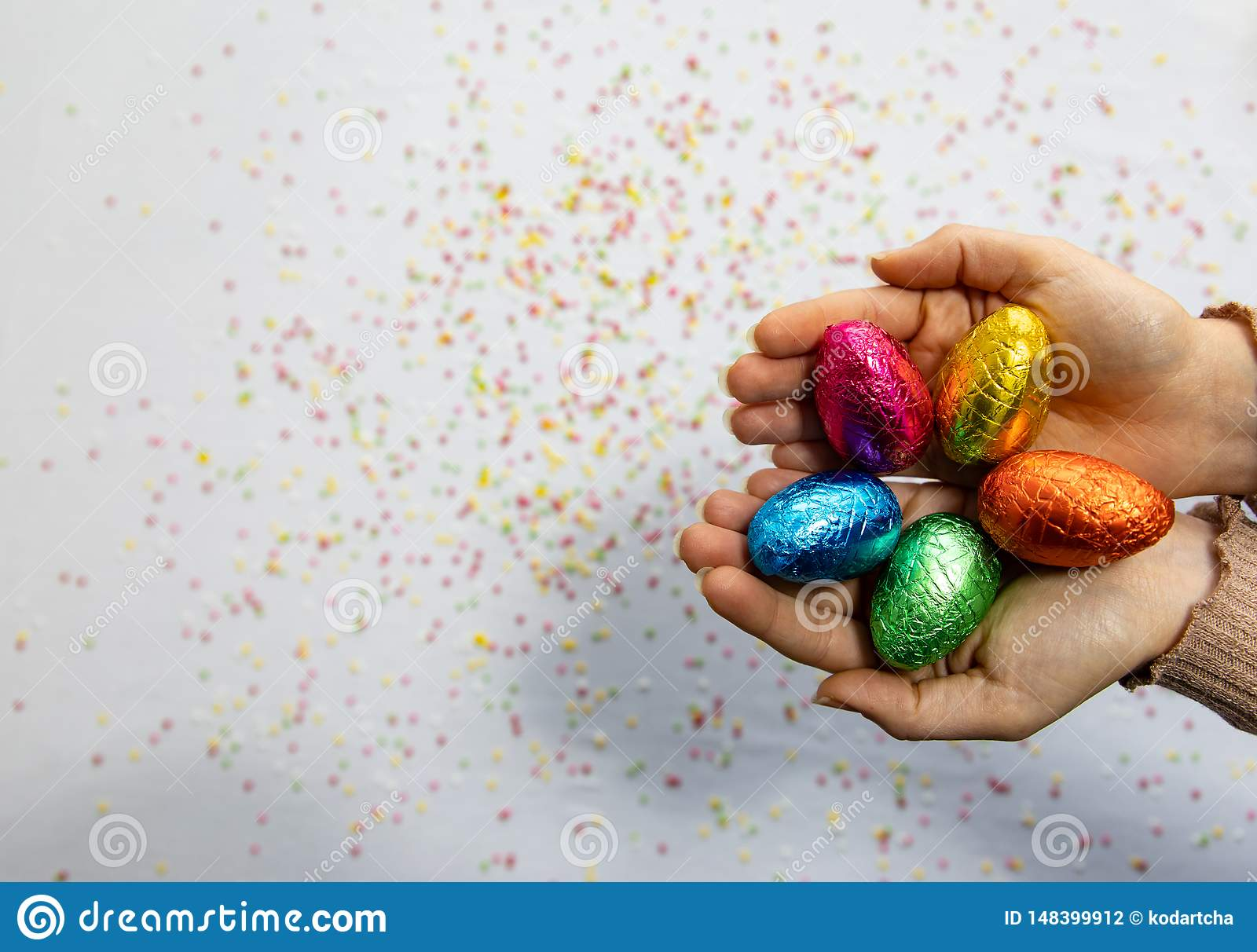 Mains de femme tenant les oeufs de p?ques color?s de chocolat avec le fond blanc et les confettis brouill?s color?s