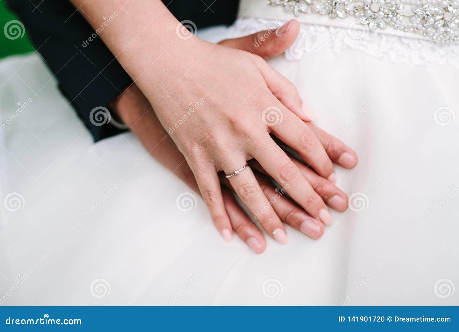 Mains de jeunes mariés ensemble