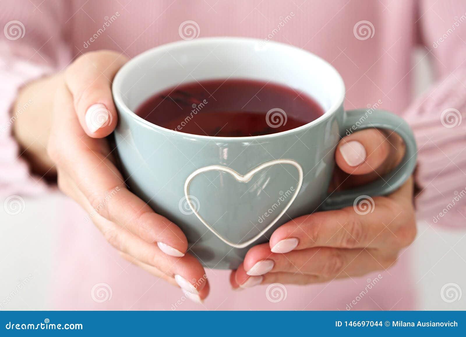 Mains de la femme s tenant la grande tasse avec le coeur