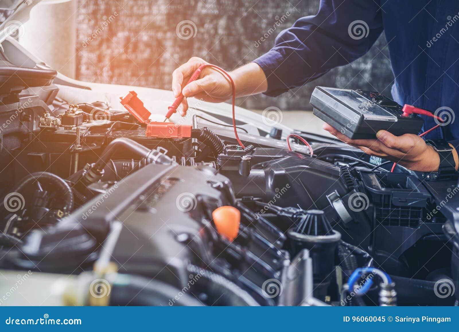 Mains de mécanicien de voiture fonctionnant le service des réparations automatique