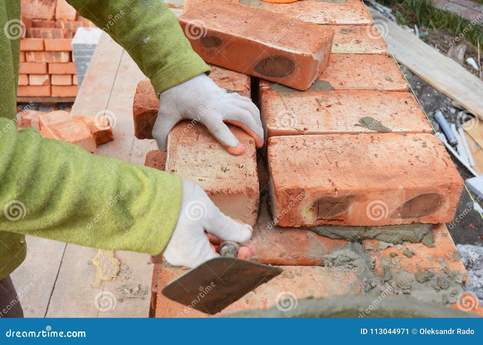 Mains de maçons dans la maçonnerie de gants de maçonnerie sur le chantier de construction de Chambre Maçonnerie, brique