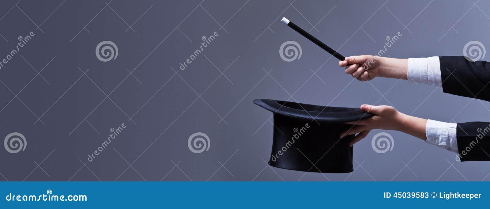 Mains de magicien avec le chapeau et la baguette magique de magie