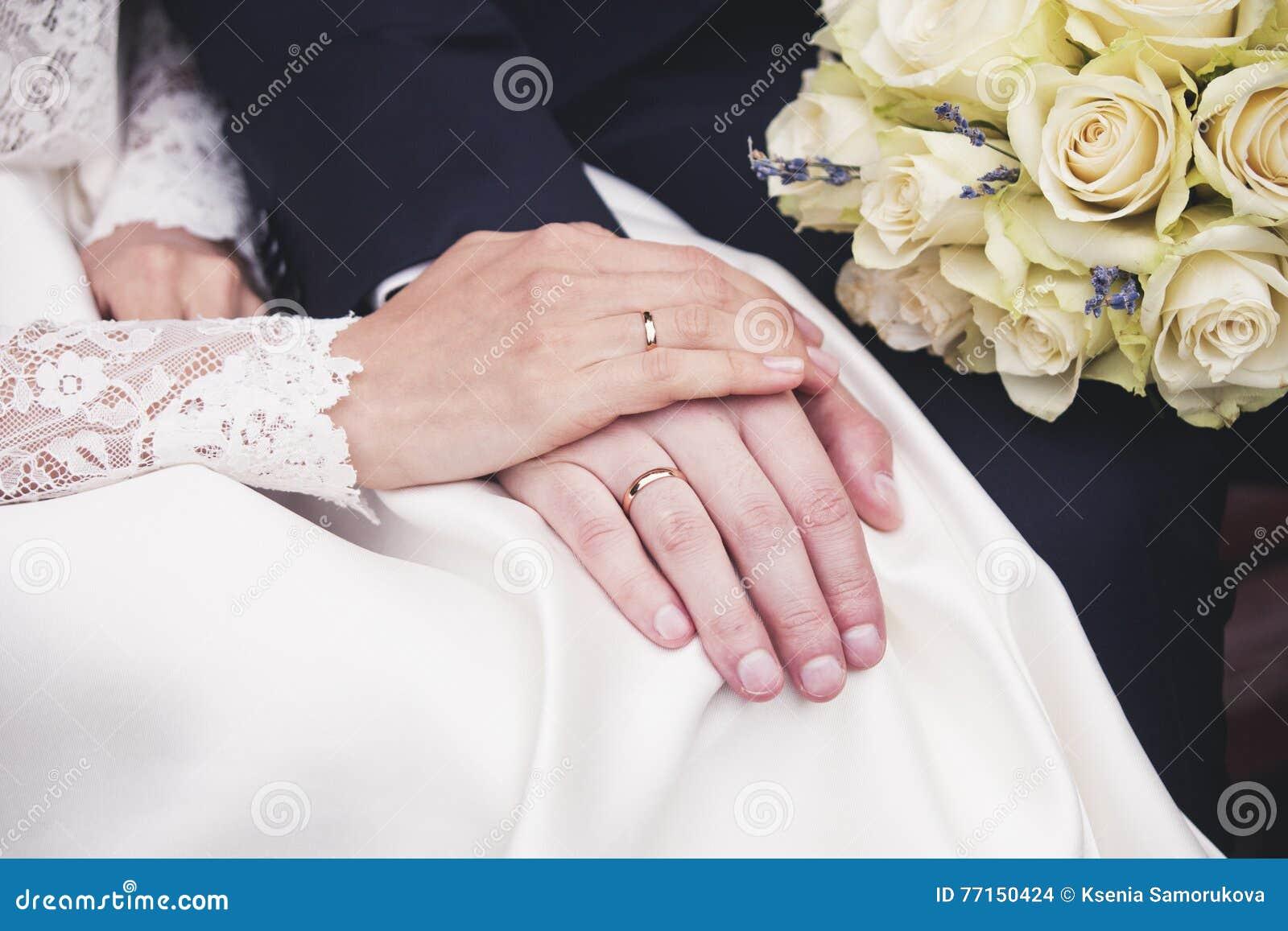 Mains de nouveaux mariés avec des anneaux de mariage