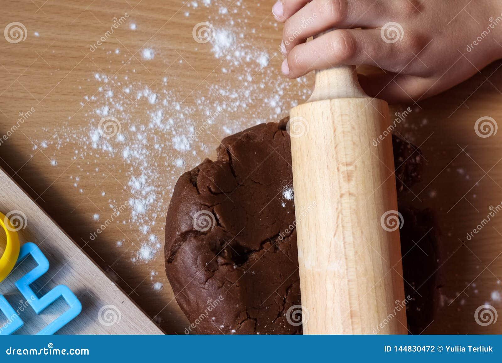 Mains de p?te de recouvrement de petite fille avec la goupille Cuisson des biscuits traditionnels de P?ques Concept de nourriture