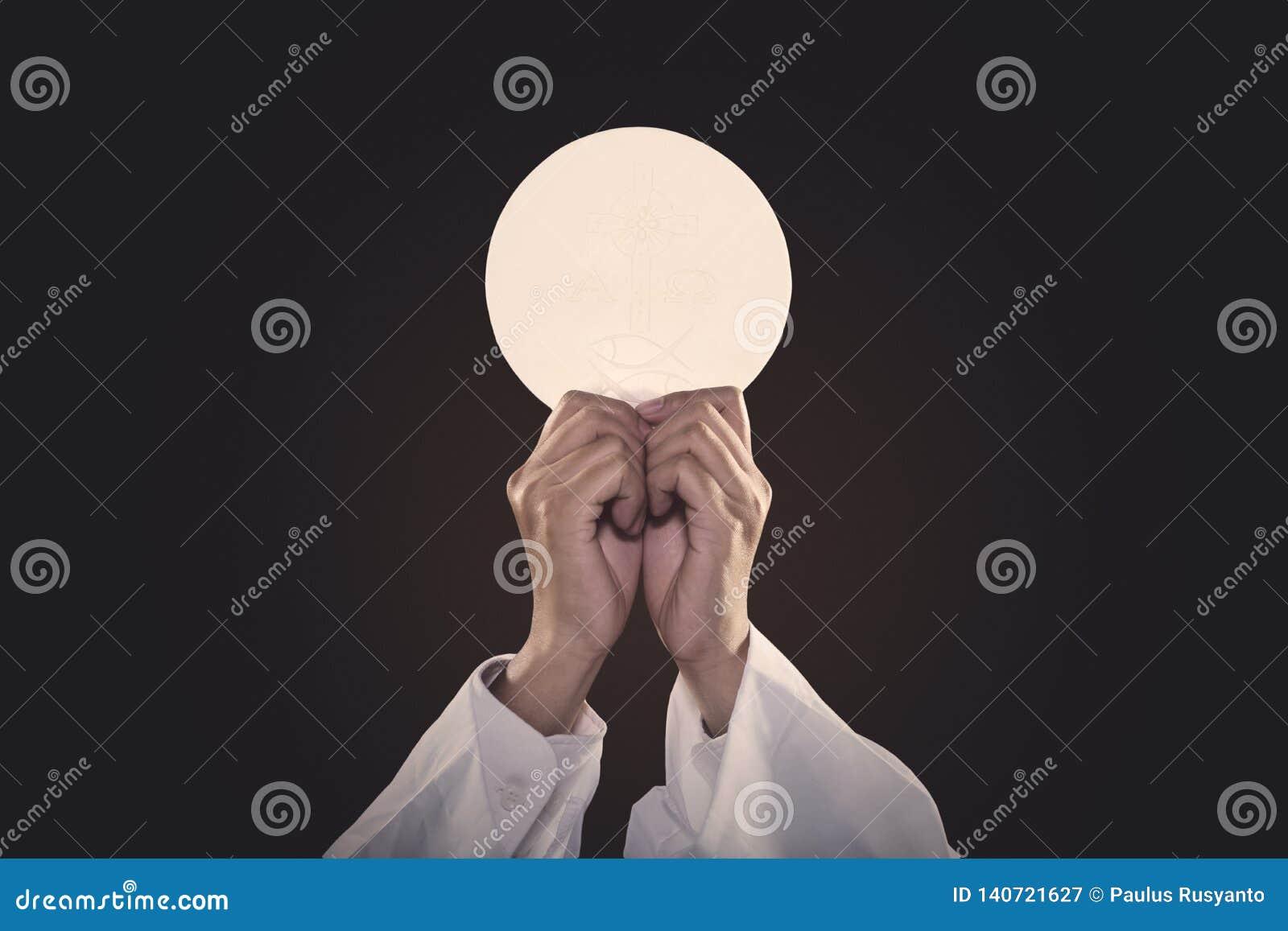 Mains de prêtre soulevant un pain de communion