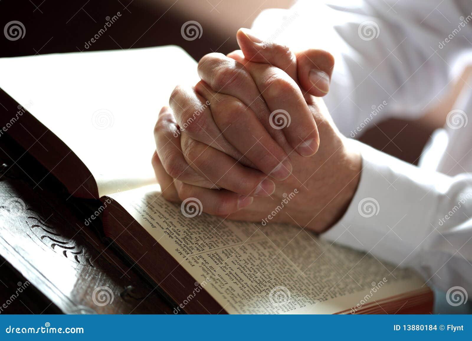 Mains de prière sur une bible ouverte