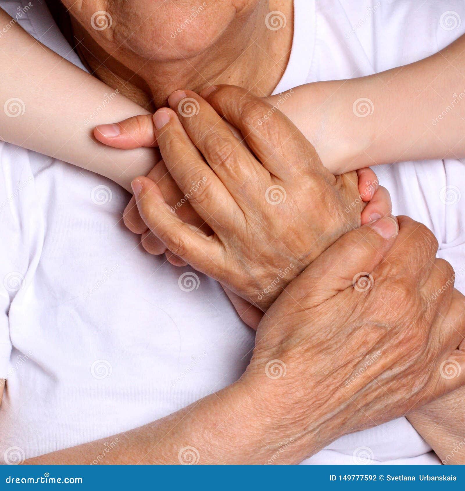 Mains de prise de grand-mère et de petite-fille avec grand amour