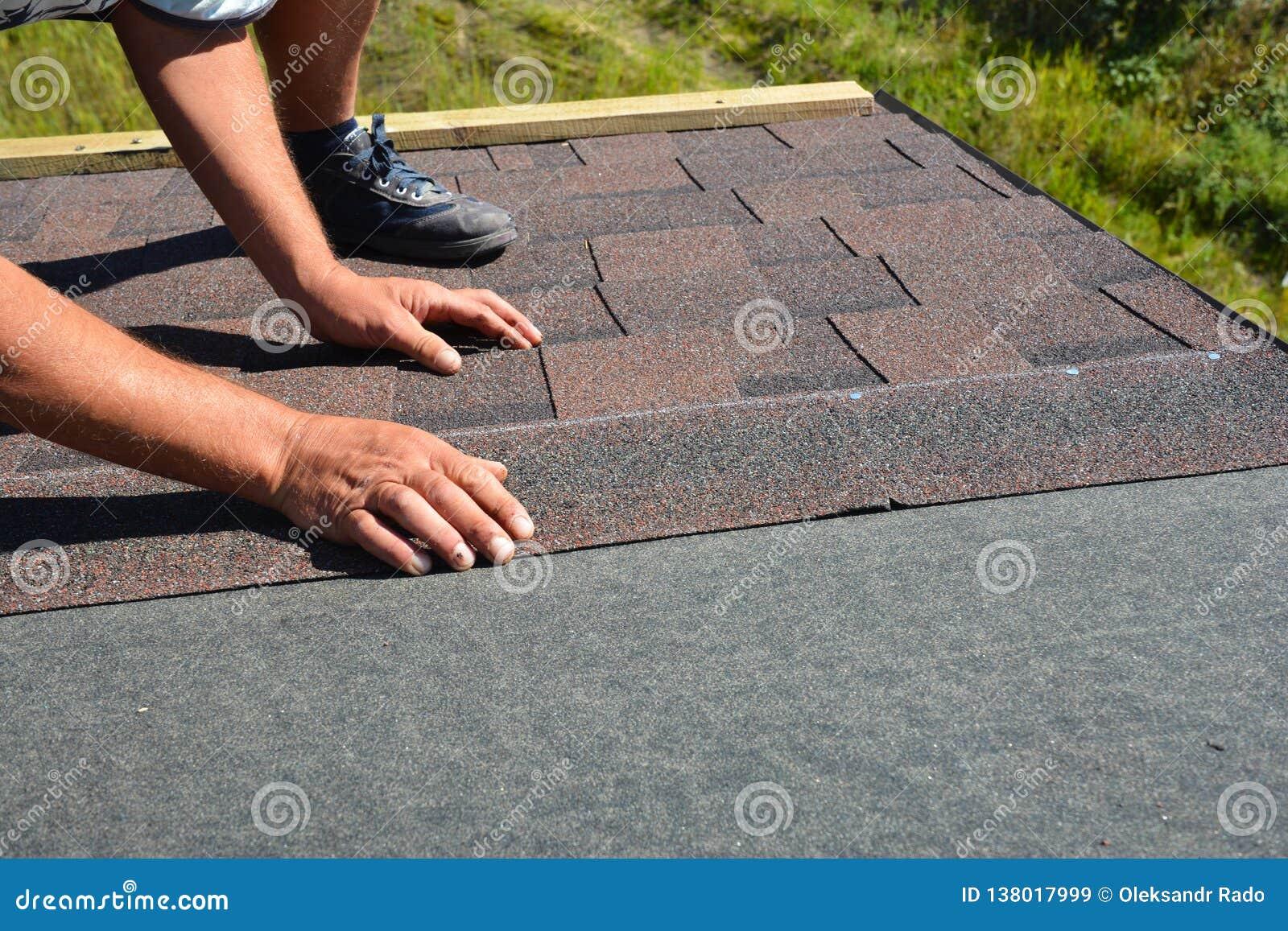 Mains de Roofer étendant Asphalt Shingles sur le toit de construction de maison Construction de toiture avec des bardeaux d aspha