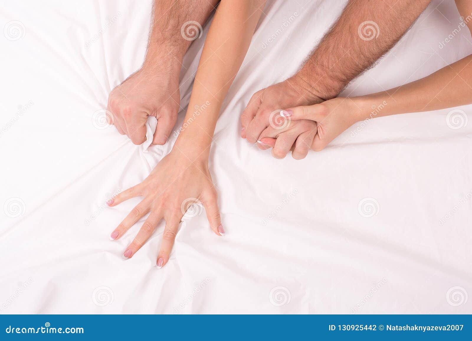 Mains des couples que la fabrication de l amour dans le lit sur le blanc a chiffonné la feuille, foyer sur des mains