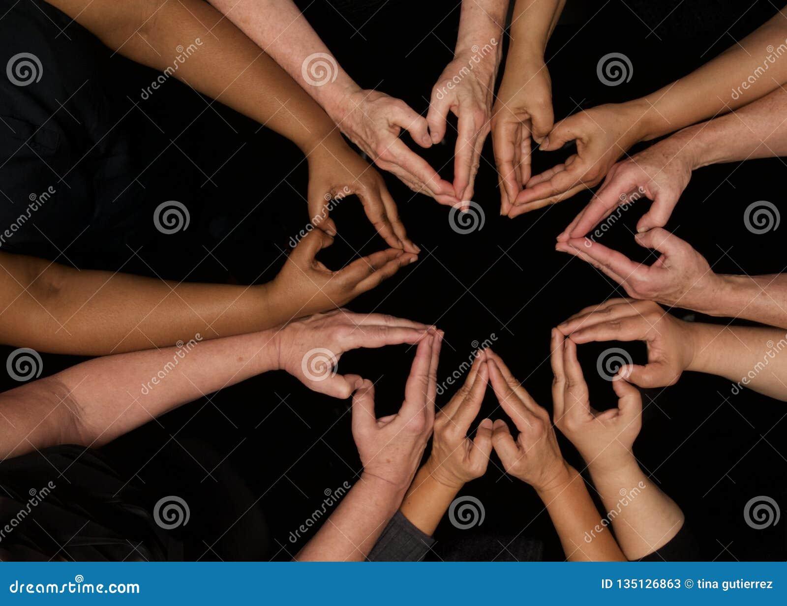 Mains des femmes de diversité travaillant coopérativement des mains aux coeurs
