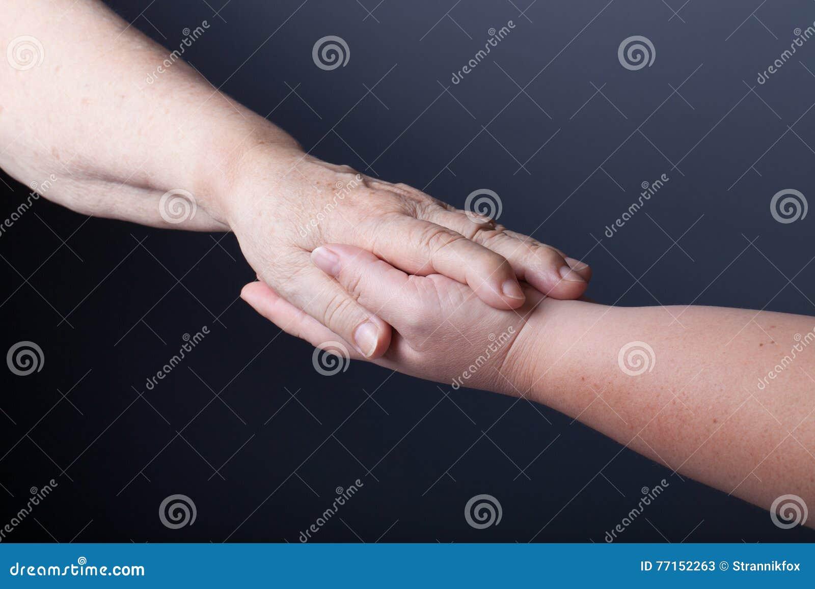 Mains des personnes âgées et des jeunes femmes sur le fond noir