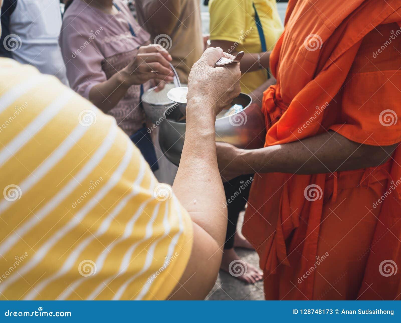 Mains des personnes tandis que la nourriture mise à l aumône du ` un s de moine bouddhiste roulent à la fin de Lent Day bouddhist