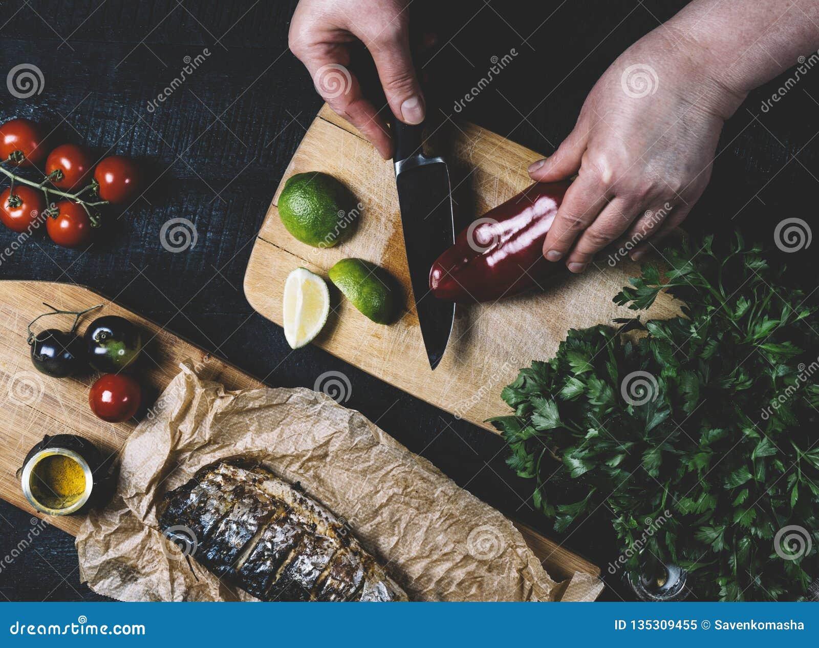 Mains en cours de faire cuire des poissons, poivre, persil, tomate, chaux sur une planche à découper sur un horiz en bois noir de