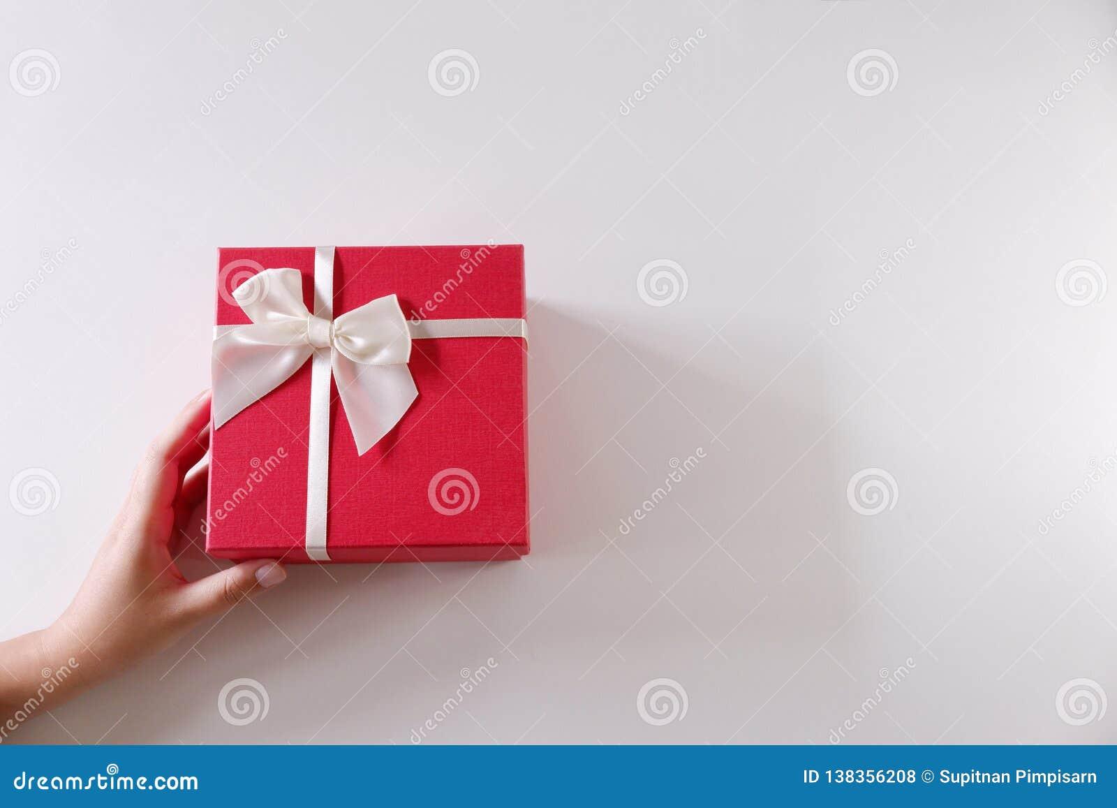 Mains en gros plan de femmes envoyant le boîte-cadeau rouge avec le ruban blanc sur le fond blanc