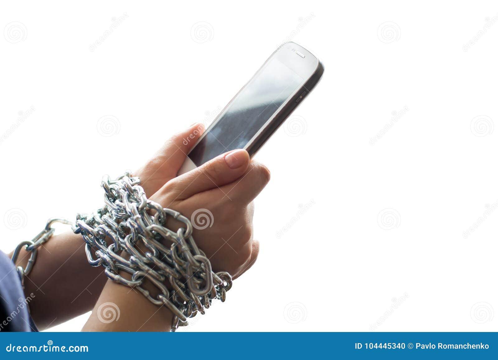 Mains enchaînées par une chaîne jugeant un téléphone portable d isolement sur le fond blanc