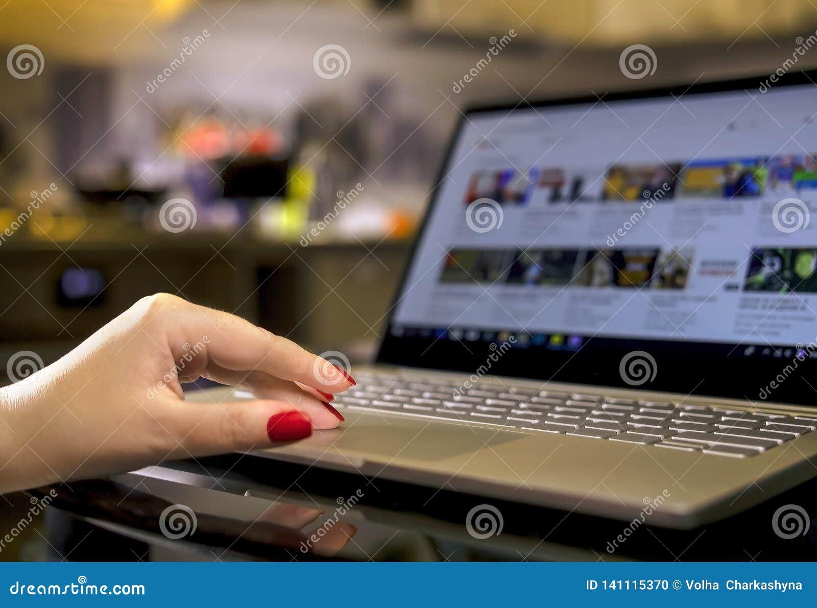 Mains femelles avec la manucure lumineuse sur un clavier d ordinateur portable le soir à la maison