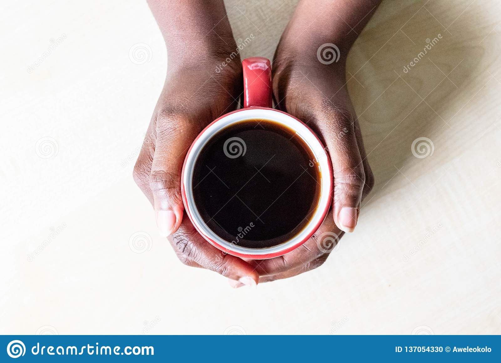 Mains femelles d afro-américain tenant la tasse rouge d expresso ou de cappuccino de café dessus sur la partie supérieure du comp