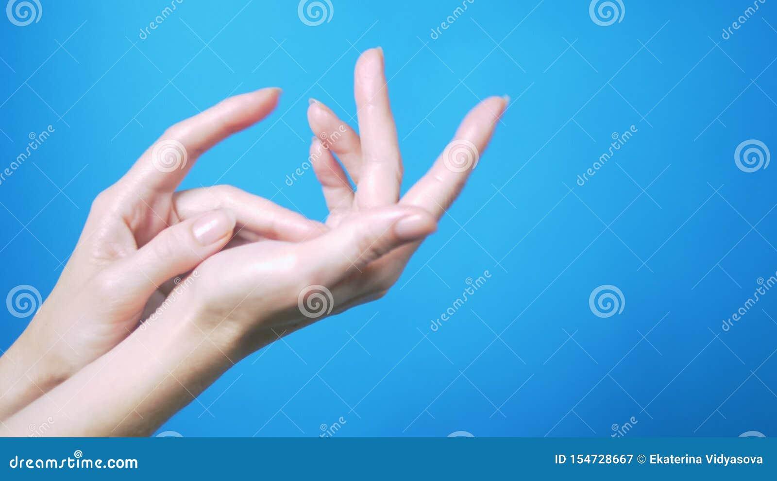Mains femelles douces avec le mouvement naturel de manucure admirablement sur un fond bleu Place pour le texte
