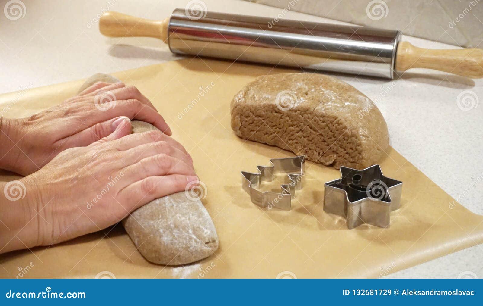 Mains femelles malaxant la pâte de pain d épice pour le gâteau de Noël