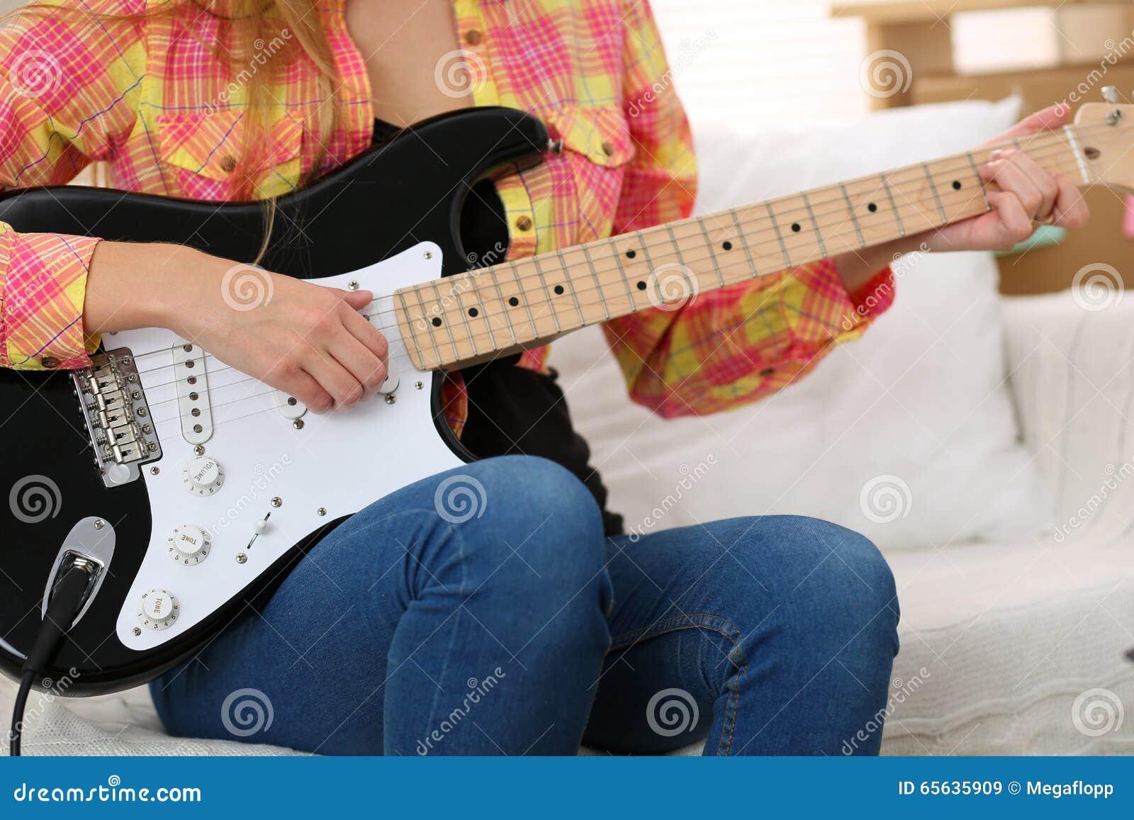 Mains femelles tenant et jouant le plan rapproché noir de guitare électrique