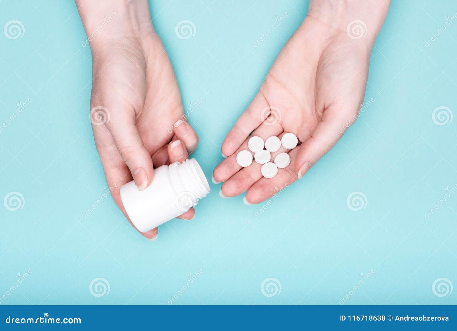 Mains femelles tenant la bouteille de médicament et les pilules blanches au-dessus du fond bleu en pastel Médicament de prise pat