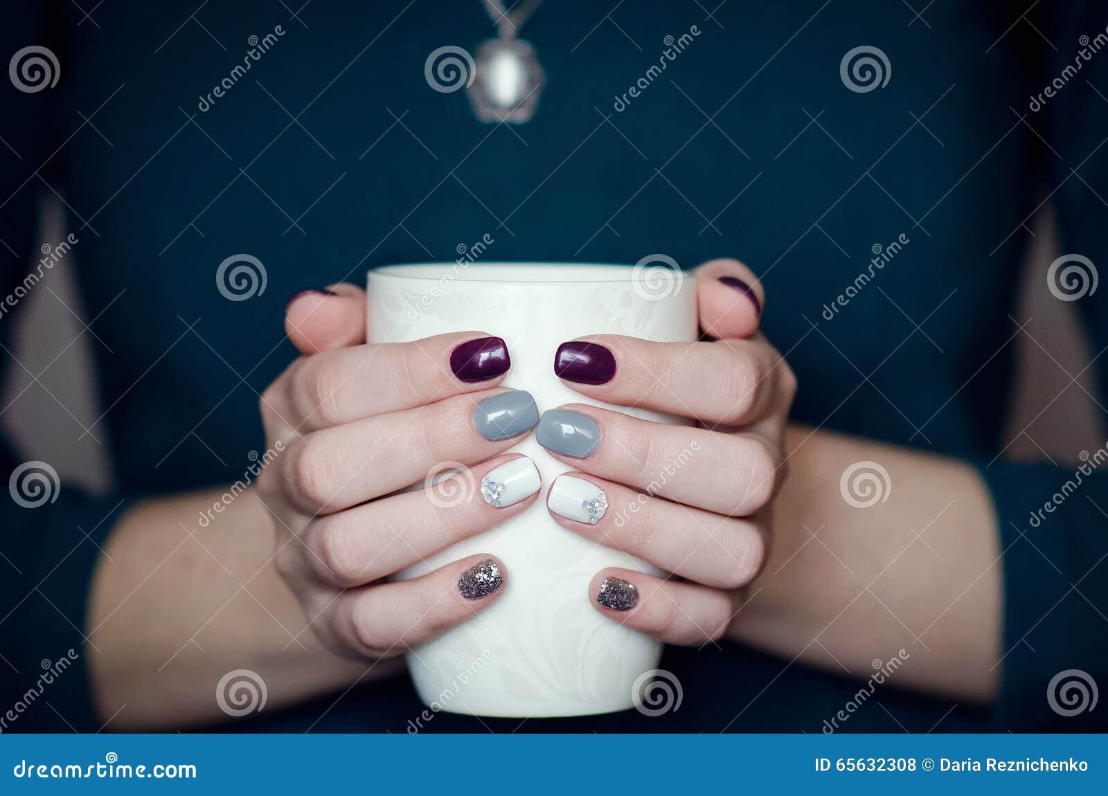 Mains femelles tenant une tasse blanche
