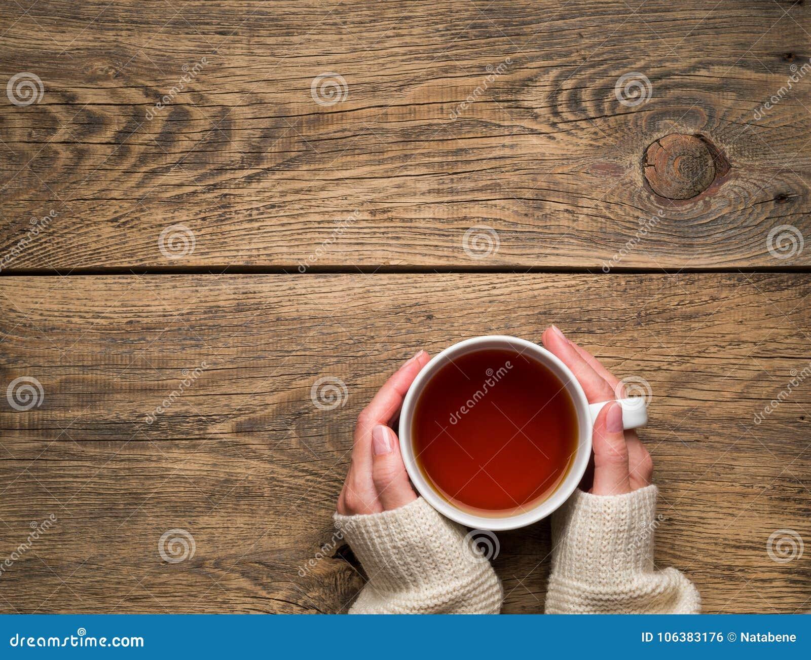 Mains femelles tenant une tasse de thé noir chaud Hiver froid W blanc