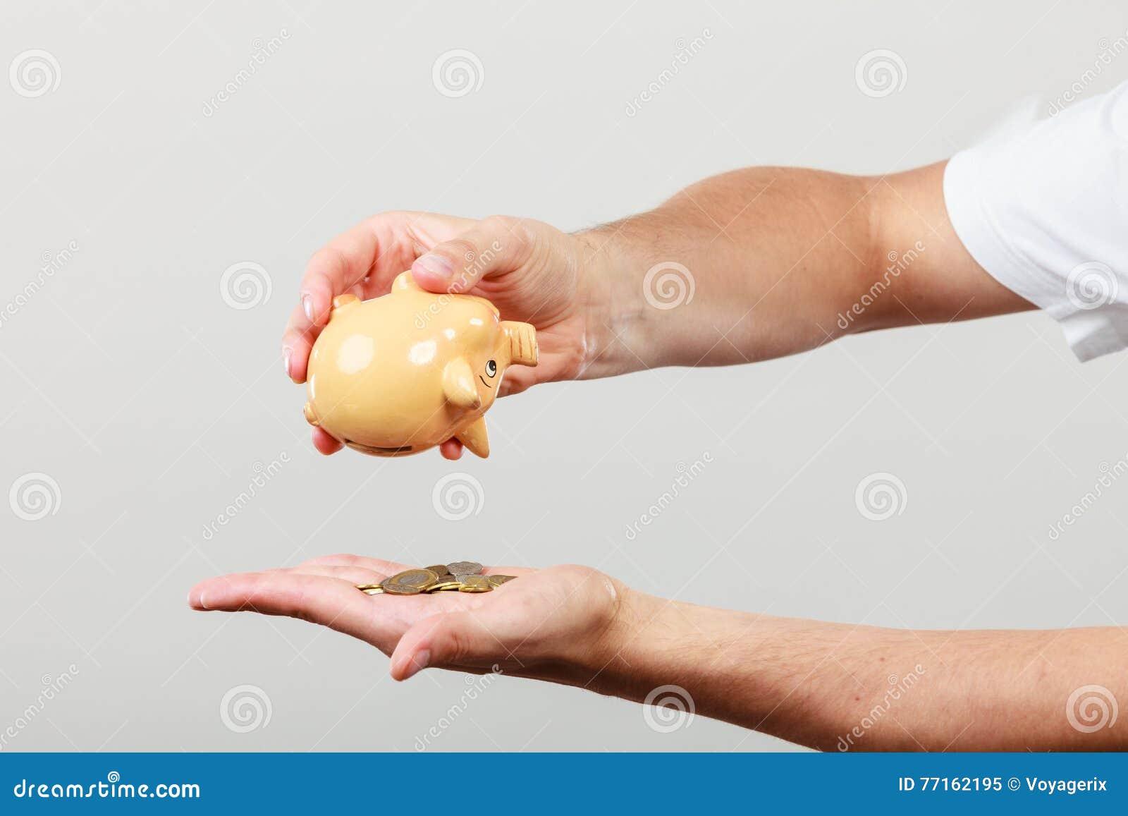 Mains masculines avec des pièces de monnaie et la tirelire