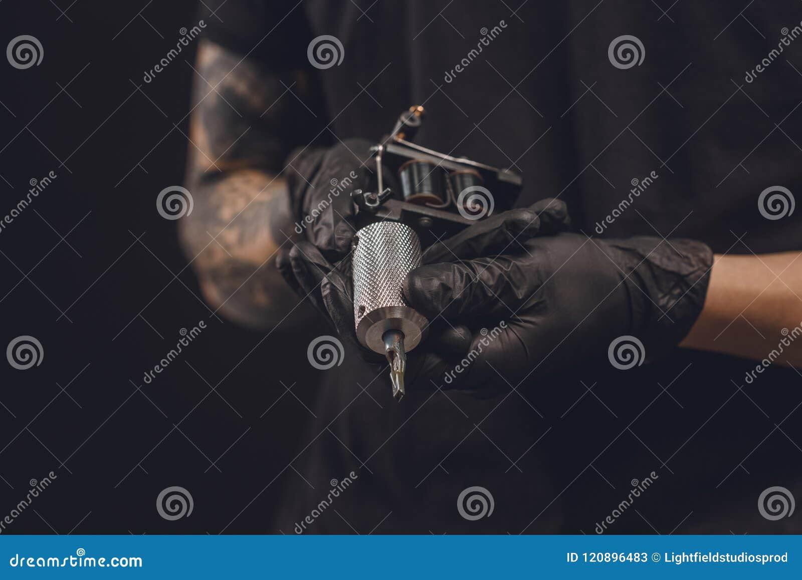 Mains masculines dans les gants tenant la machine de tatouage