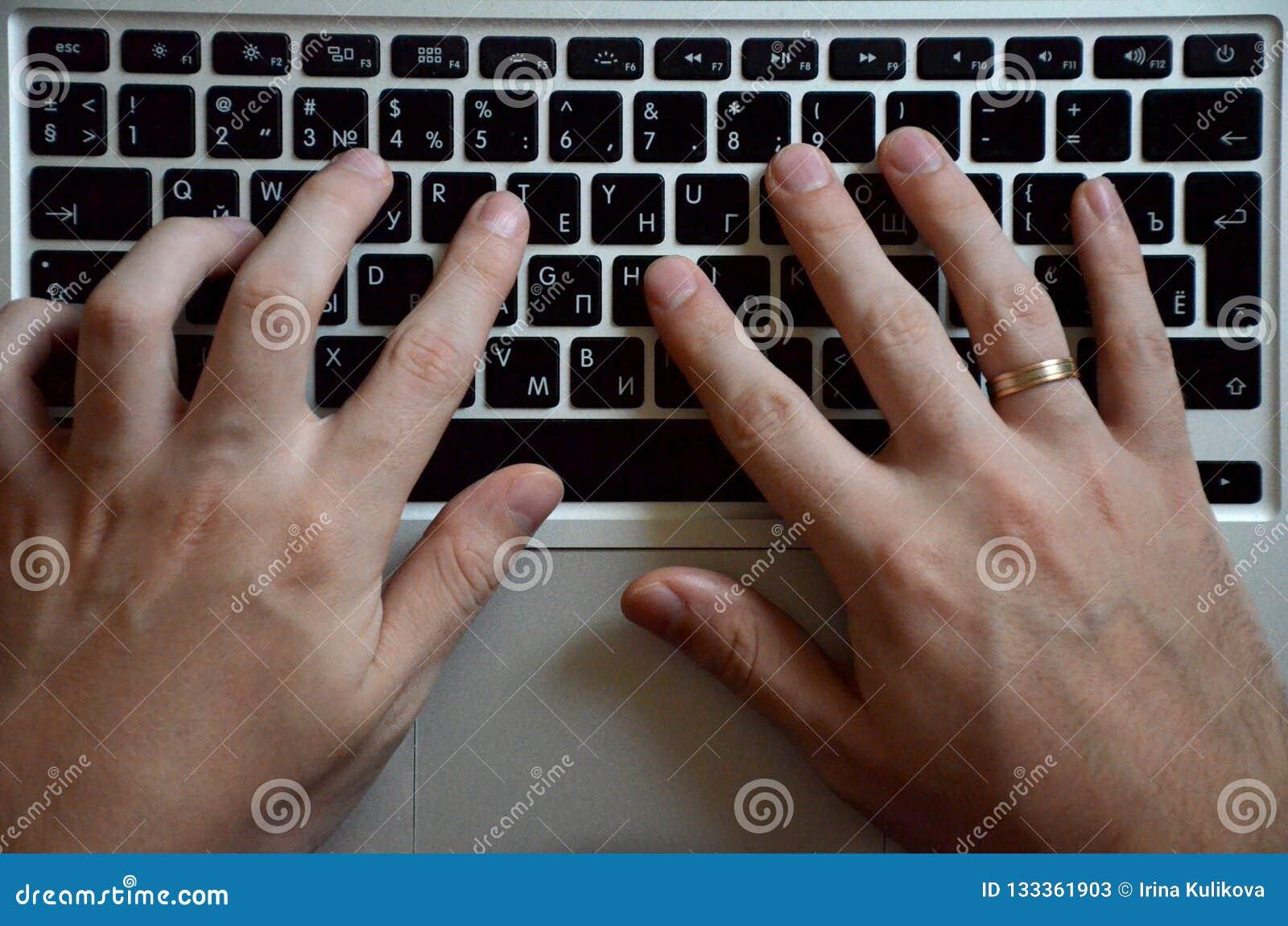 Mains masculines sur un clavier noir Travail européen sur un ordinateur