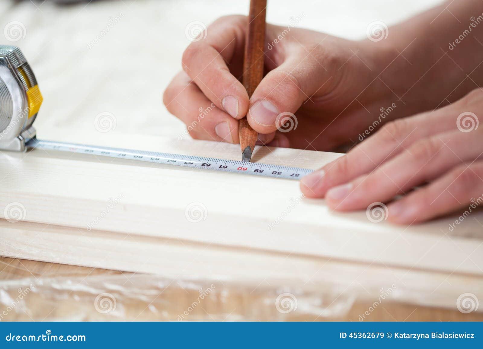 Mains masculines utilisant la bande de mesure sur le conseil en bois